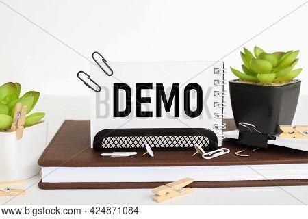 Demo. Business Card Holder On A Work Table, On A Notebook, Near A Flowerpot