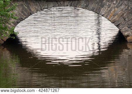 Stonework Of A Bridge Pylon Of A 19th Century Brick Bridge. Old Stone Bridge And A River