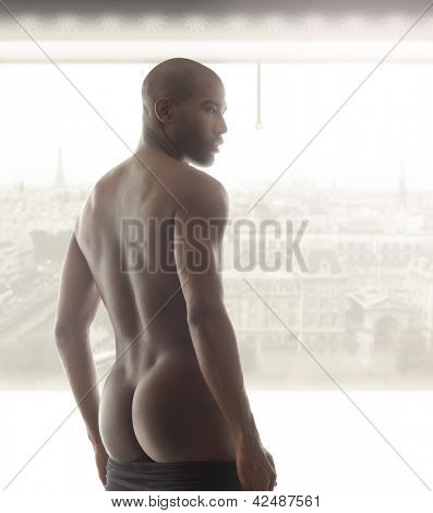 Portrait of a beautiful male model from behind against bright window
