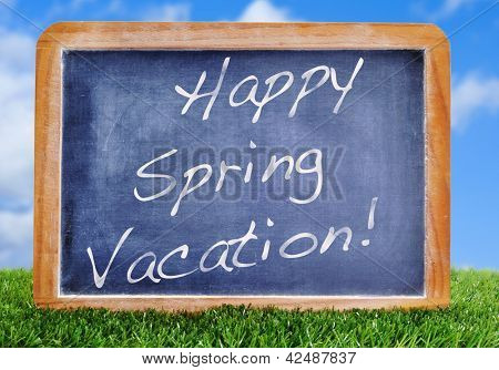 Happy spring vacation written in a blackboard on the grass