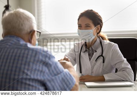 Smiling Doctor In Facemask Handshake Mature Male Patient
