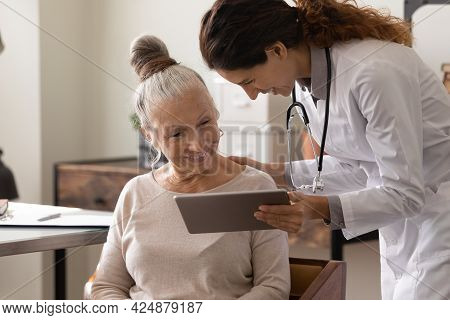 Female Doctor Use Tablet At Consultation With Mature Patient