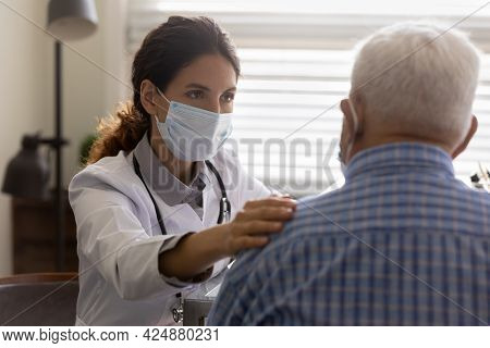 Caring Doctor In Facemask Support Old Male Patient