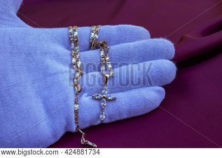 Christian Cross With A Gold Chain On The Palm Of A Man. Human Hand. Christian Cross. Golden Chain. O
