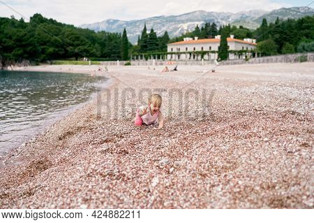 Little Girl Crawls Along A Pebble Beach Near The Water. Villa Milocer