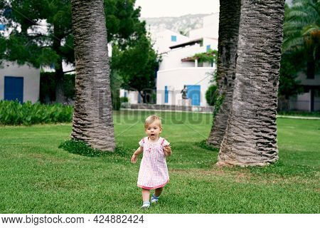Little Girl With An Open Mouth Walks On A Green Lawn Against The Backdrop Of Huge Date Palms