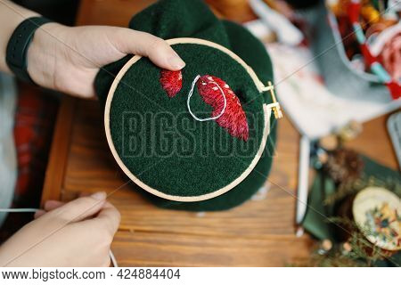 Girls Hands Embroidery Fly Agaric Hat On Frame. Wooden Table With Different Objects On Background. C
