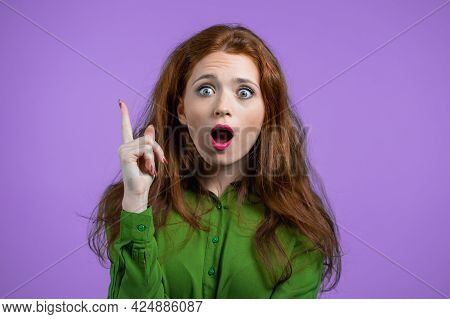 Portrait Of Young Woman Having Idea Moment Pointing Finger Up On Violet Studio Background. Smiling H