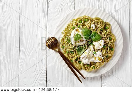 Spaghetti Salad With Pesto Sauce, Green Peas, Basil Leaves And Burrata Cheese On A White Plate On A