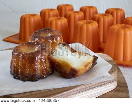 Caneles With A Soft And Tender Custard Center And A Thick Caramelized Crust On A Wooden Board And Or