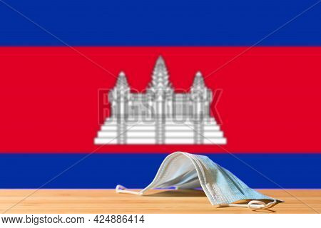 A Medical Mask Lies On The Table Against The Background Of The Flag Of Cambodia. The Concept Of A Ma