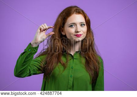 Young Woman Showing Invisible Abstract Small Subject Or Object. Tiny Concept. Violet Studio Backgrou