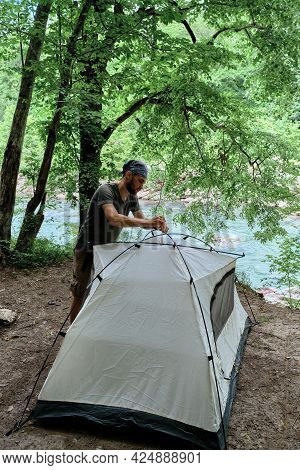 Put Tourist Tent In Campsite And Prepare For Rest. Young Handsome Caucasian Male Traveler With Banda