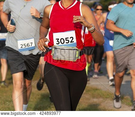 Close Up Of Runners Racing A 5k In A Trail With A Women Wearing A Fanny Pack Around Her Waist To Car