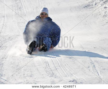 Man Sledding Down The Hill