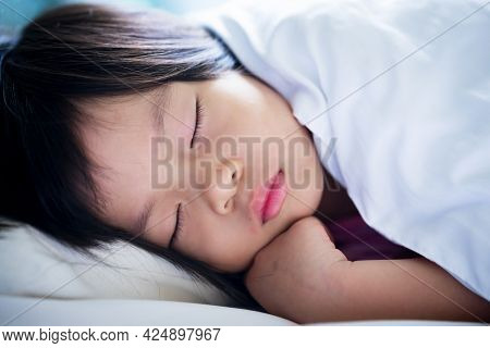 Headshot Of Child Girl Sleep On Her Bed. Close Up Little Kid Sleeping With Close Eyes While Taking A