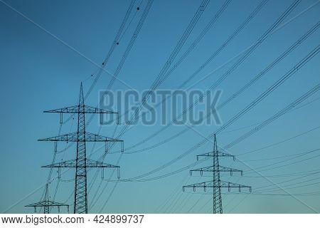 Crossing Electric Pylon In Blue Sunset Sky
