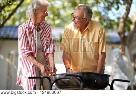 elderly caucasian couple looking each other and smiling, while making fire for barbeque