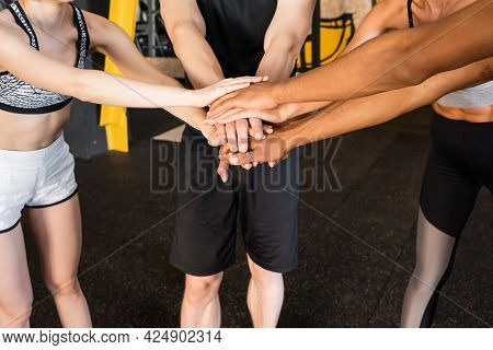 Partial View Of Young Multiethnic Sports People Joining Hands In Gym