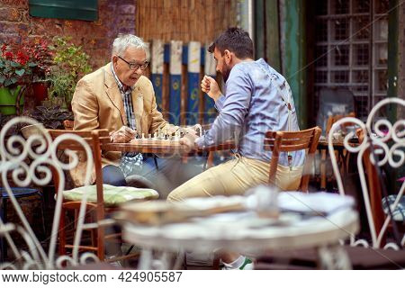 young beardy guy playing chess with elderly man, sitting in outdoor cafe. selective focus image