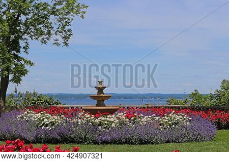 Colorful Flowers In Public Park With Retro Fountain And Sea In Background