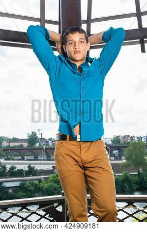 Dressing In A Blue Shirt, Brown Pants, Two Hands Putting On The Back Of The Head, A Young Attractive