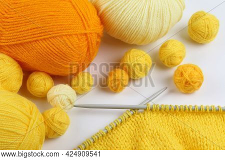 A Lot Of Yellow Balls Of Yarn For Knitting Or Crocheting And An Unfinished Knitted Product On Gray K