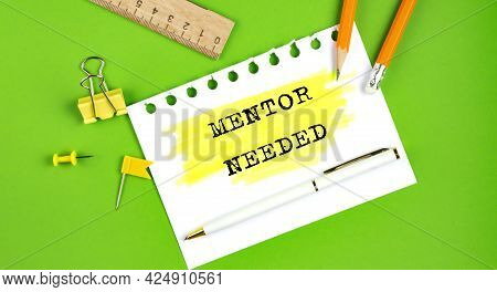 Text Mentor Needed Sign Showing On The Green Background With Office Tools