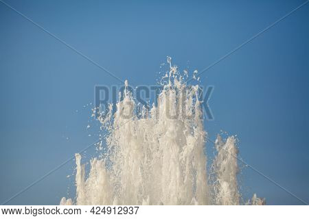 Large Jet Of Water From The Fountain On A Blue Background. Space For Text.