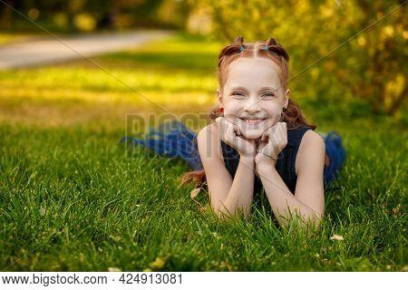 A Beautiful Little Redhead Girl In A Blue Dress Lies On The Grass In A City Park On A Warm Summer Da