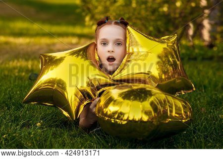 A Beautiful Little Girl With Bright Yellow Balloons In A Blue Dress Lies On The Grass In A City Park