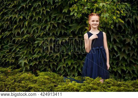 Portrait Of A Beautiful Little Red-haired Girl In A Blue Dress Outdoors In A City Park On A Warm Sum