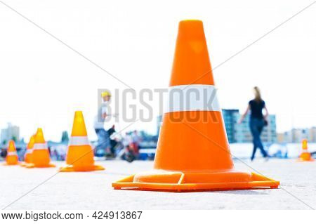 Road Cones Of Orange Plastic On The Background Of People And The City. Repair Work On City Streets.