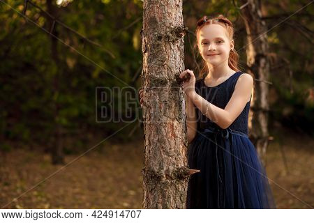 Portrait Of A Beautiful Little Red-haired Girl In A Blue Dress Outdoors In A City Park On A Warm Aut