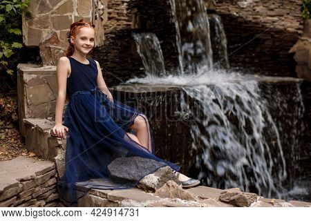 A Beautiful Little Red-haired Girl In A Blue Dress Sits Against The Background Of An Artificial Wate