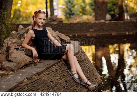 A Beautiful Little Redhead Girl In A Dress Sits By The Water In A City Park On A Warm Autumn Day. Ch