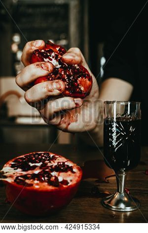 Male Hands Squeeze A Juicy Pomegranate And Juice Flows From It. Dark Red Liqueur. Hard Alcohol Aesth
