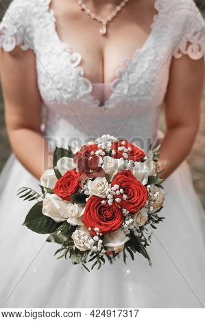 A Bride In A Wedding Dress Holds A Decorative Wedding Bouquet Of Flowers Of Red And White Roses In H