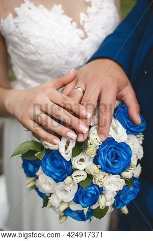The Hand Of The Bride And Groom At The Wedding Put Their Hands On A Bouquet Of Flowers Roses Close U