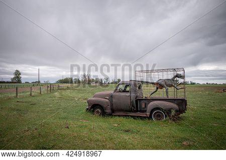 Patricia, Alberta - June 5, 2021: An Old Abandoned Gmc Truck Wtih A Caged Dinosaur Near Dinosaur Pro