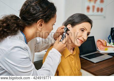 Hearing Exam For Elderly Citizen People. Otolaryngologist Doctor Checking Mature Womans Ear Using Ot