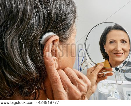 Mature Woman With Bte Hearing Aid Looks At Herself In Mirror And Tries On Hearing Device, Close-up.