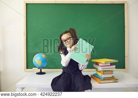Schoolgirl With Ponytails Sitting On Teacher Desk In Classroom.