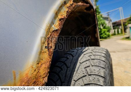 Fragment Of A Car Body With Rust. Fragment Of A Rusty Wing Of A Car. The Body Element Is Corroded. C