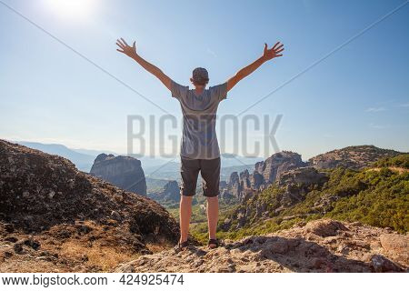 Happy Man Traveller Standing With Hands Up In Mountain