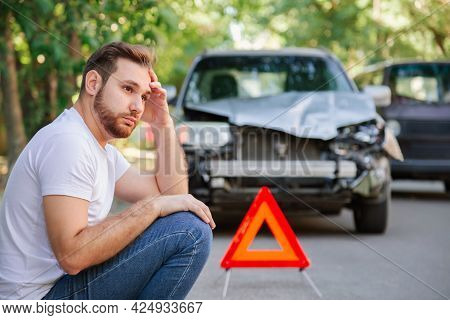 Portrait Of Upset Man Sitting On Road Near Wrecked Car After Car Accident With Red Triangle. Caucasi