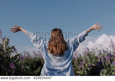Unrecognizable Woman With Arms Outstretched Standing Alone Among Field Of Purple Flowers In Front Of