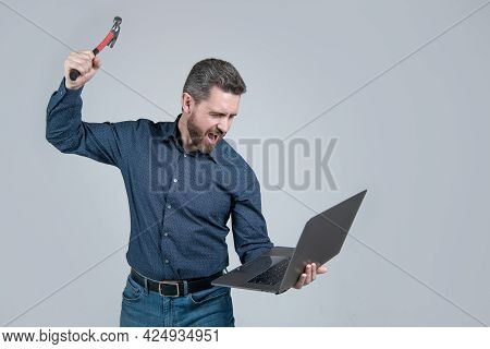 Releasing Anger On Computer. Stressed Man Yelling And Breaking Laptop With Hammer. Got Stressed