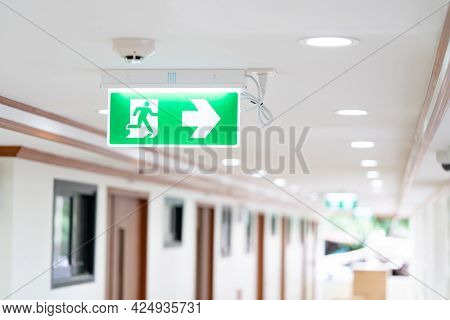A Arrow Light Box Sign Of Emergency Fire Exit Is Hung On The Ceiling In Hospital Walkway, Idea For E