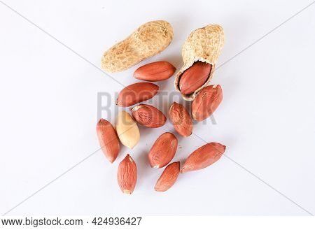 Red And Peeled Peanuts On A White Background. One Peanut Was Peeled, Revealing A Red Seed Inside.